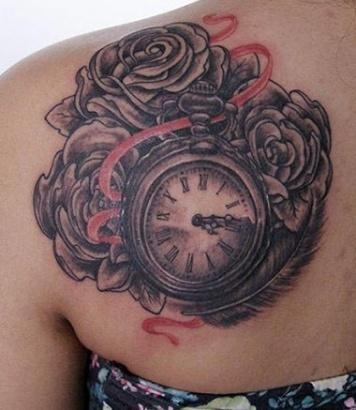 тату карманные часы с тремя розами, перо и красная лента на левой лопатке у девушки