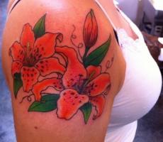Тату две красные лилии на плече