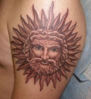 тату солнце с лицом на плече