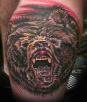 Тату голова медведя с открытой пастью на колене