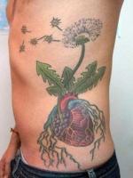 Тату зеленый одуванчик с корнями и летящими семенами на боку