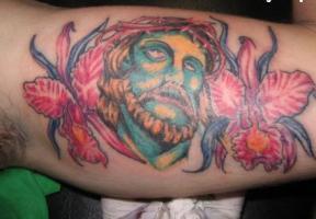 Тату голова Иисуса с терновым венцом и цветы на мышце