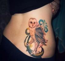 Тату белая сова с серыми крыльями - на спине у девушки