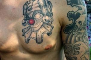 Тату серый клоун с красным носом на груди