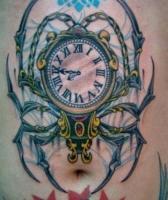 тату карманные часы с лапами паука на животе