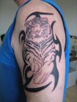 Тату тигр лежит с узором на плече