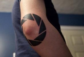 Тату круг из треугольников на локте