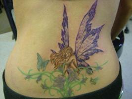 Тату на пояснице фея у цветка с бабочкой и пчелой