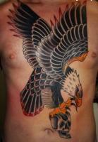 Тату большой орел держит череп - на груди
