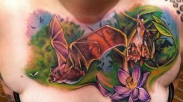 Тату летучая мышь и цветок на груди