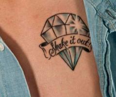 Тату алмаз и ленточка с надписью на груди