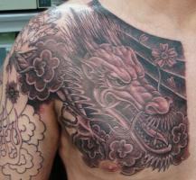 Тату голова дракона с цветами на груди